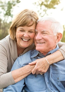 An older couple smiling and hugging outside.