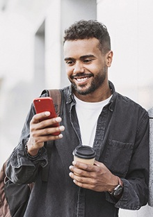 person smiling and looking at their phone while leaning against a building
