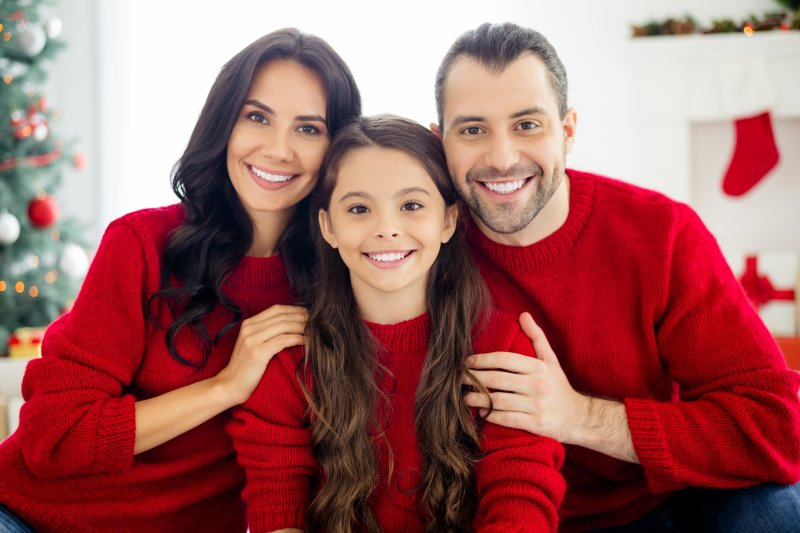 Family of three smiling with holiday decorations in background